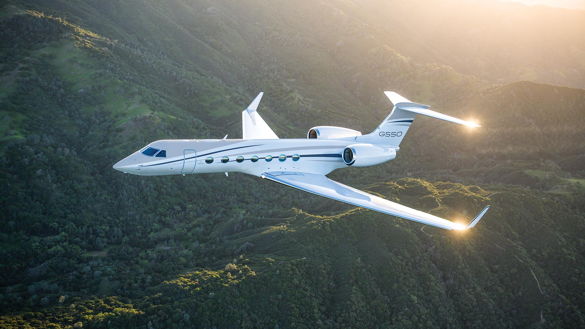 G550 aircraft flying over mountains
