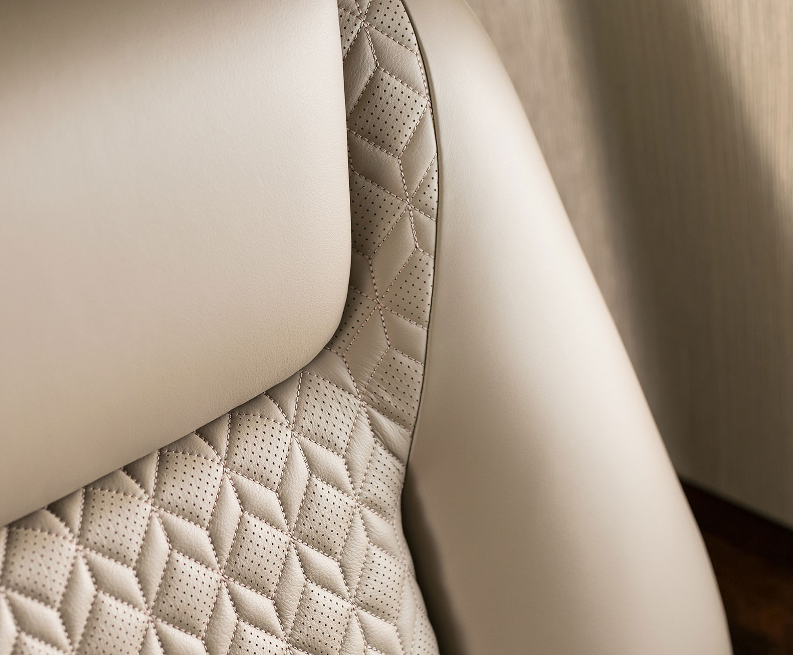 A close-up of a beige leather seat.
